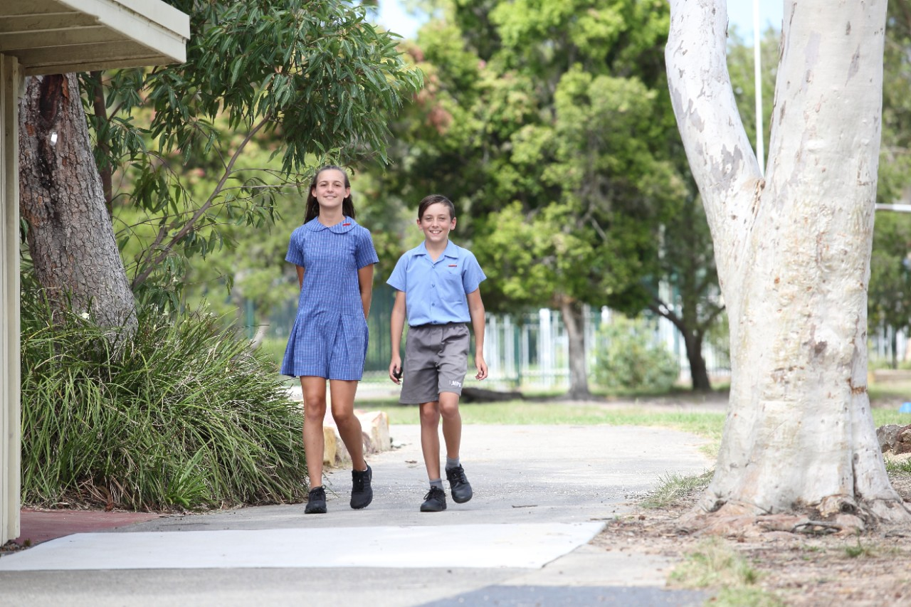Two students walking along the school path