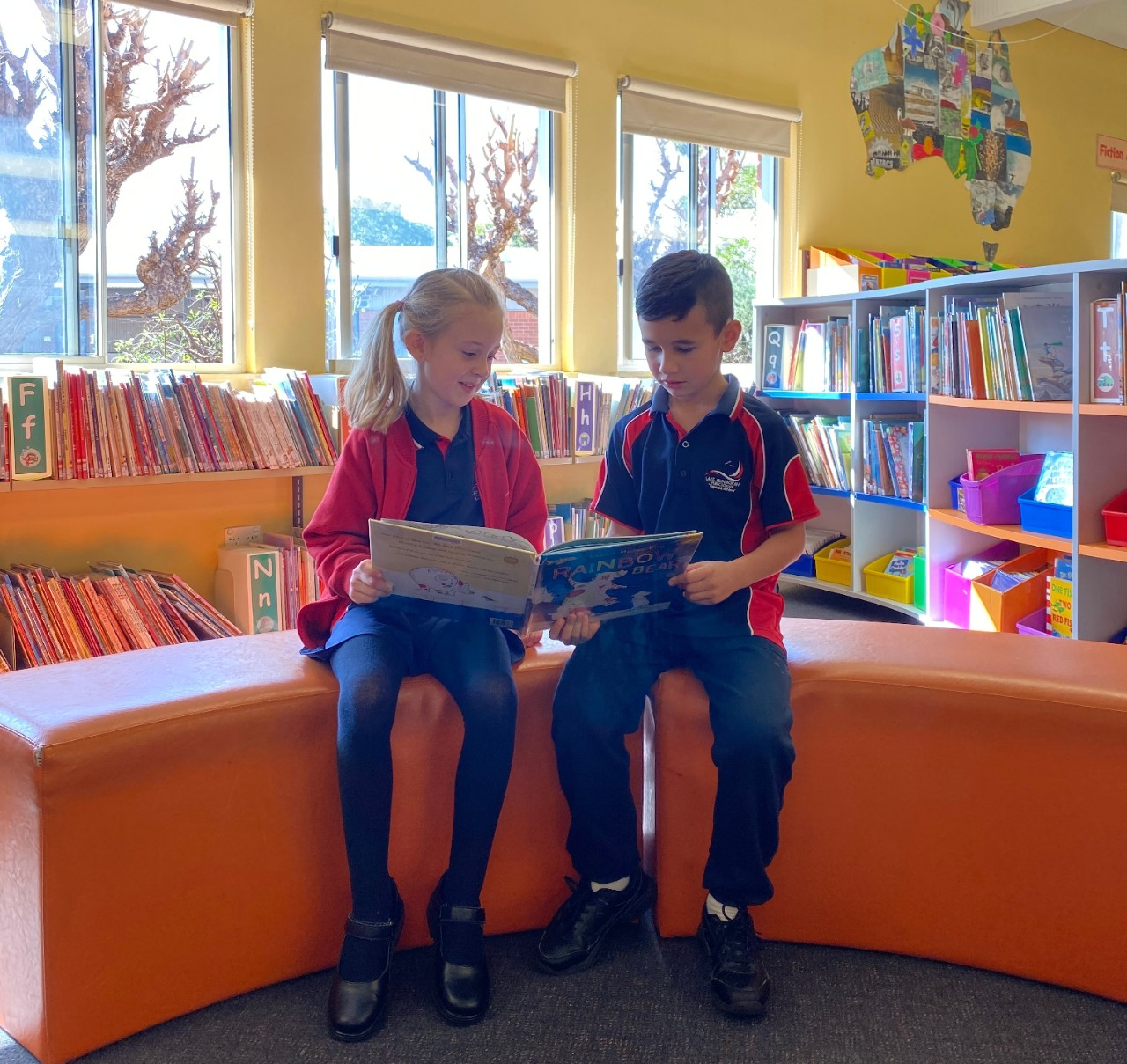 two students reading a book together in the library